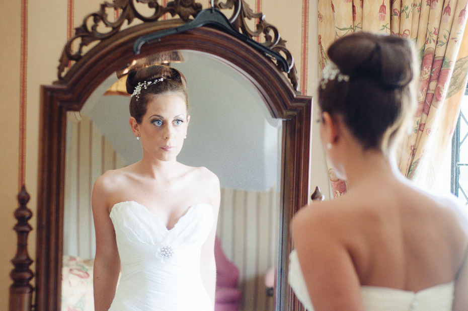 Bride looking in mirror - Groomsmen - Eastwell Manor Wedding Photographer