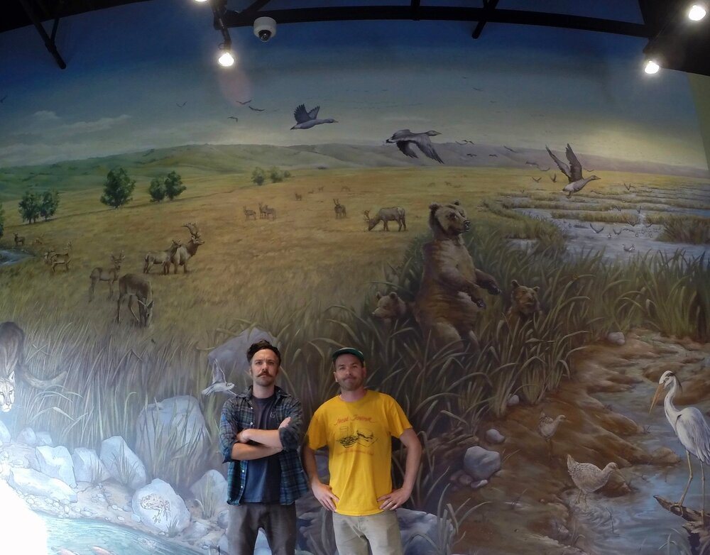 The Bristle Bros pose in front of their Hayward Area Historical Society Natural History mural.
