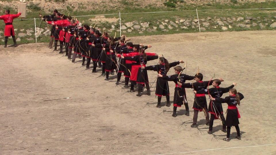Een groep boogschutters staat opgesteld in de 'arena', een rijbak op het terrein waar het trainingskamp plaatsvindt