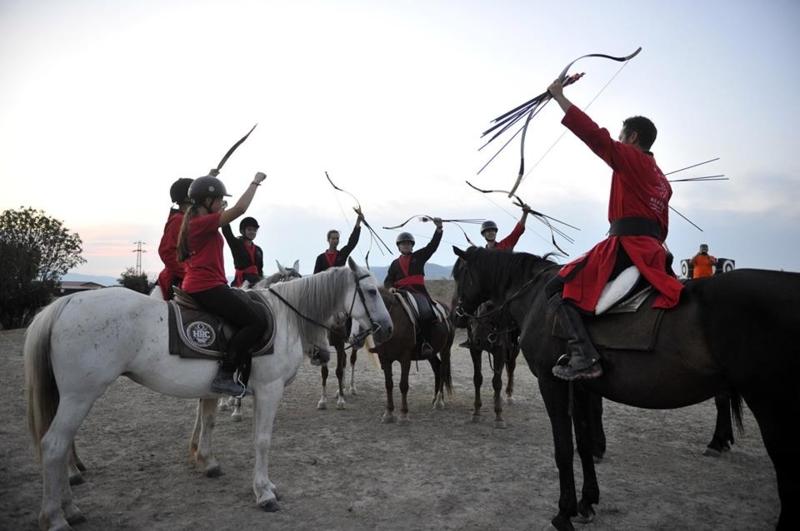 Ruiters tijdens een trainingskamp boogschieten te paard