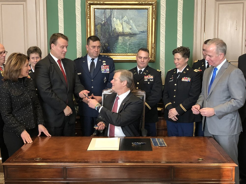 Pictured: Senator Michael Moore receives a pen at the bill signing ceremony from Governor Charlie Baker surrounded by Lt. Governor Karyn Polito, Major General Gary Keefe and legislative colleagues in the Governor's Office at the State House in Boston.