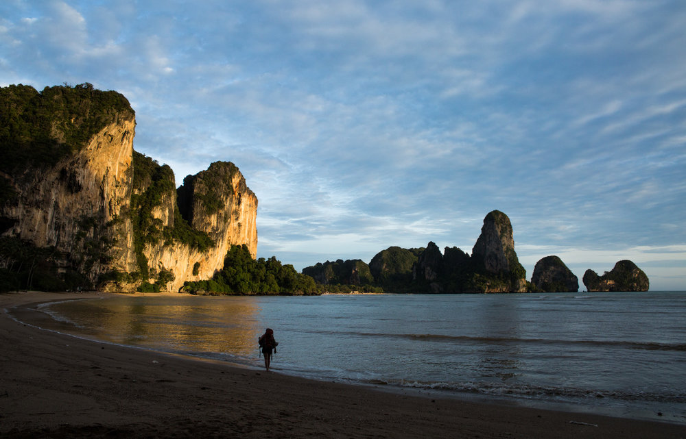 A traveller walks along the beach at Tonsai Beach, Krabi, Thailand.
