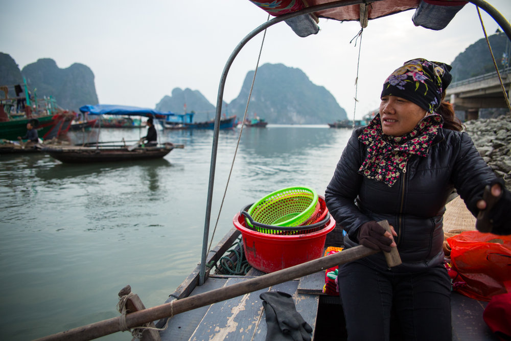 A fisherman rows her boat in Halong Bay, Vietnam.