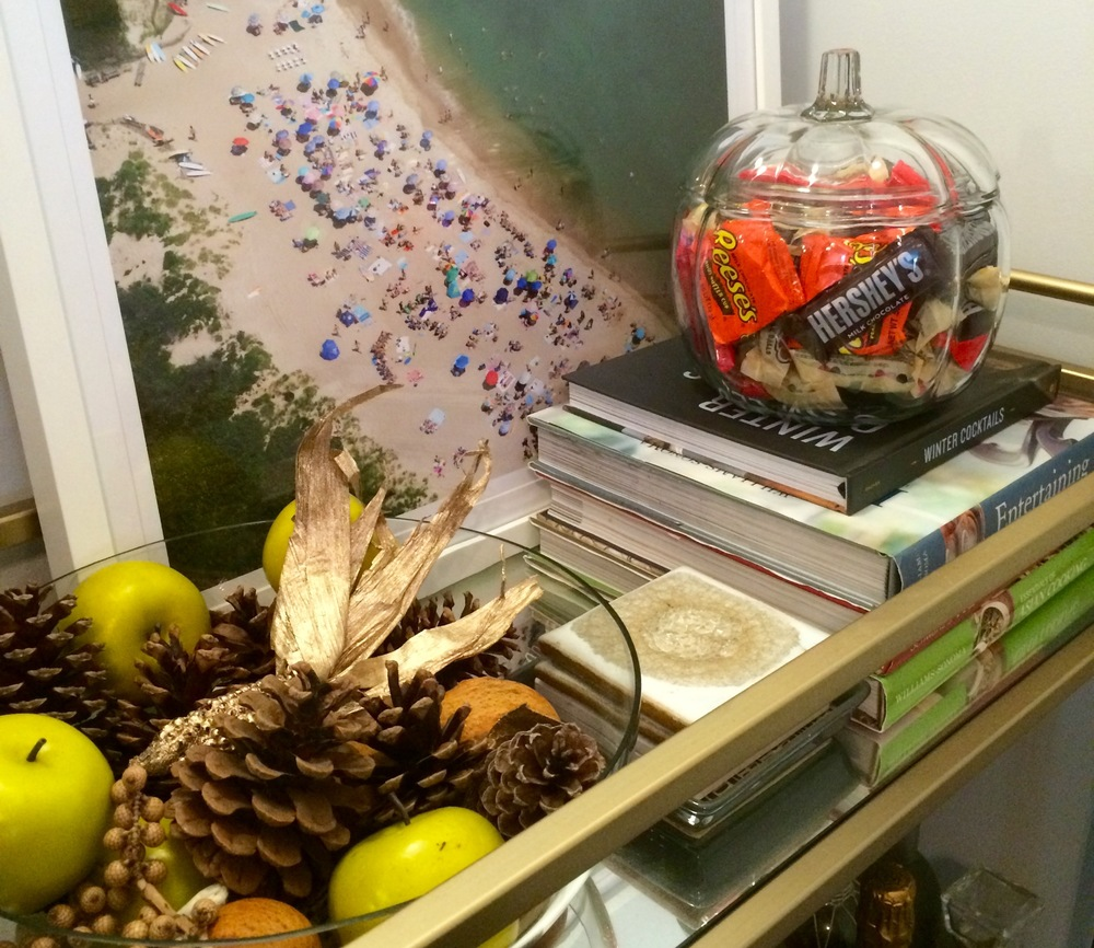 Candy, apples, and pinecones on the bar cart.