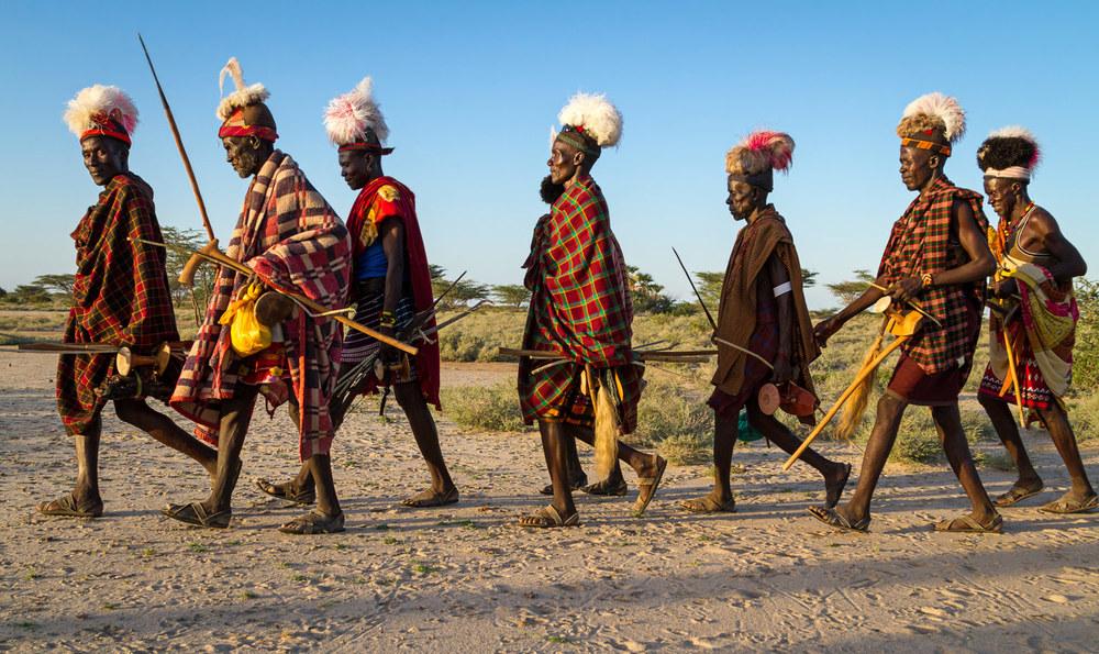 Turkana men return home from a wedding ceremony; Turkana, Kenya