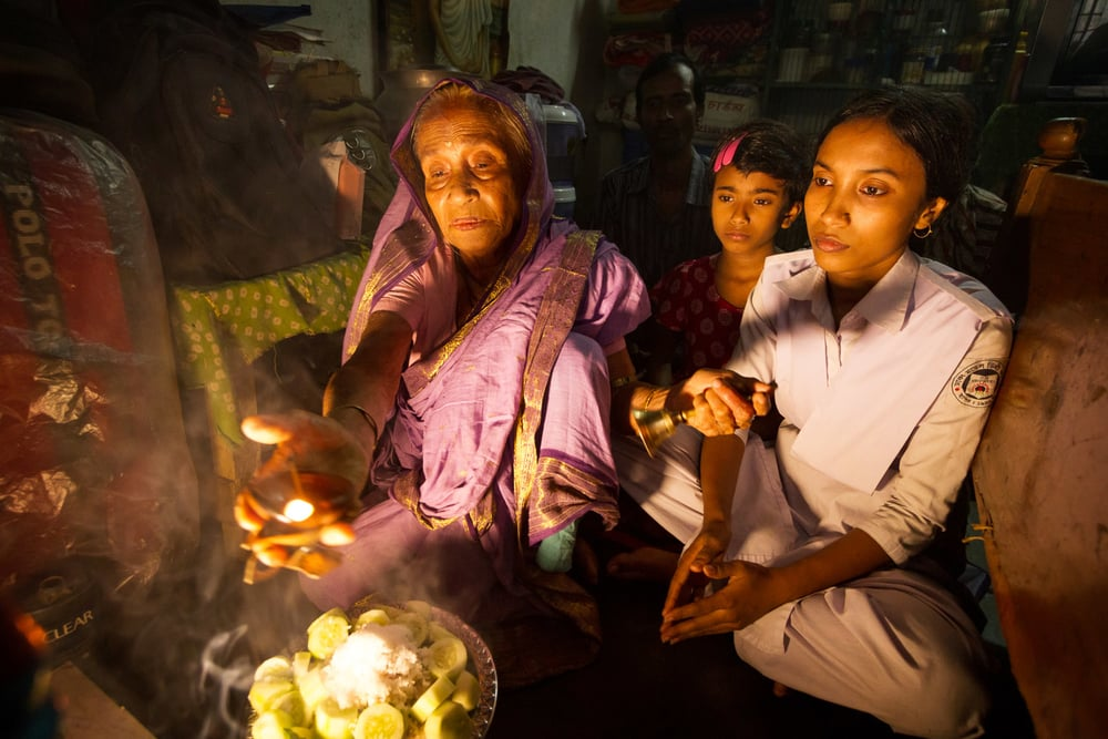 Shushmita joins her grandmother and her sister for a puja after she returns home from school.