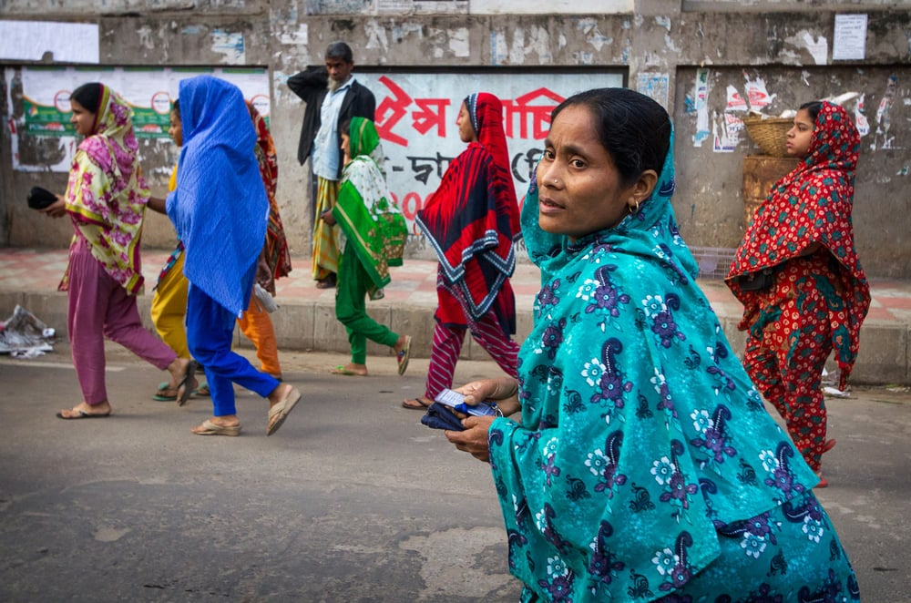 Saleha falls in with other garments workers on her way to work.    The garments sector in Bangladesh employs almost four million workers and is the largest employer of women in Bangladesh.  Employers can afford to be demanding as they have a massive pool of low-skilled labor to draw upon.