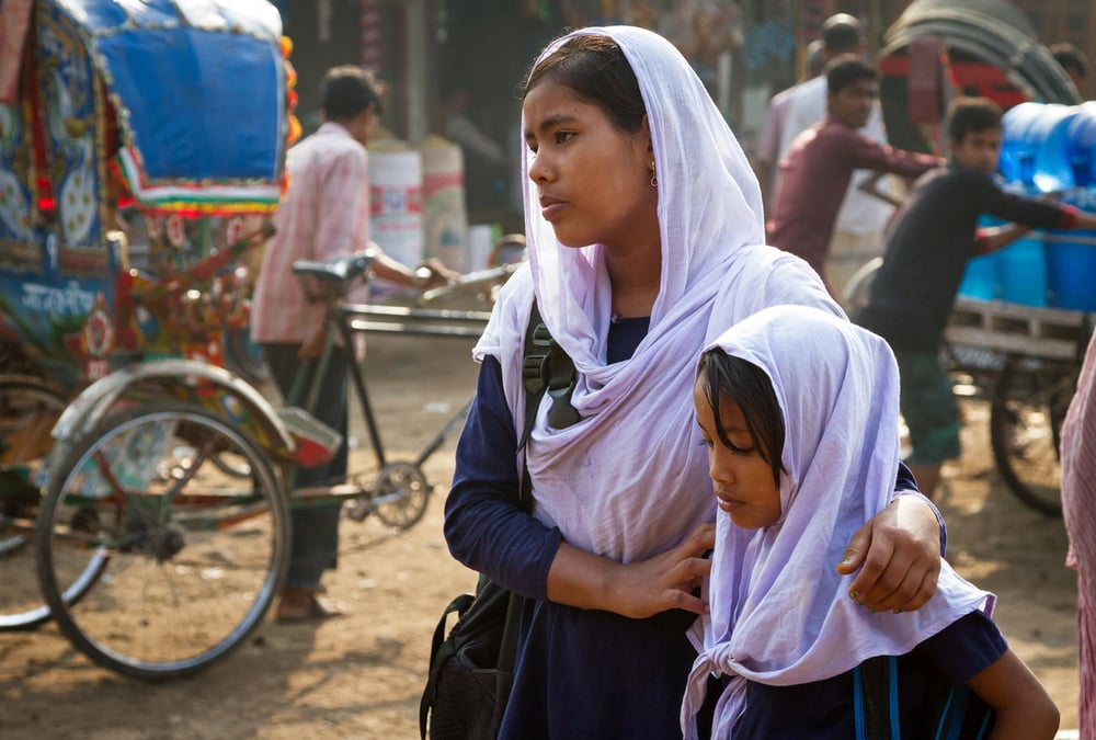 Moni and Aduri wait for their father, a rickshaw puller, to pick them up and take them to the NGO-run school they attend.