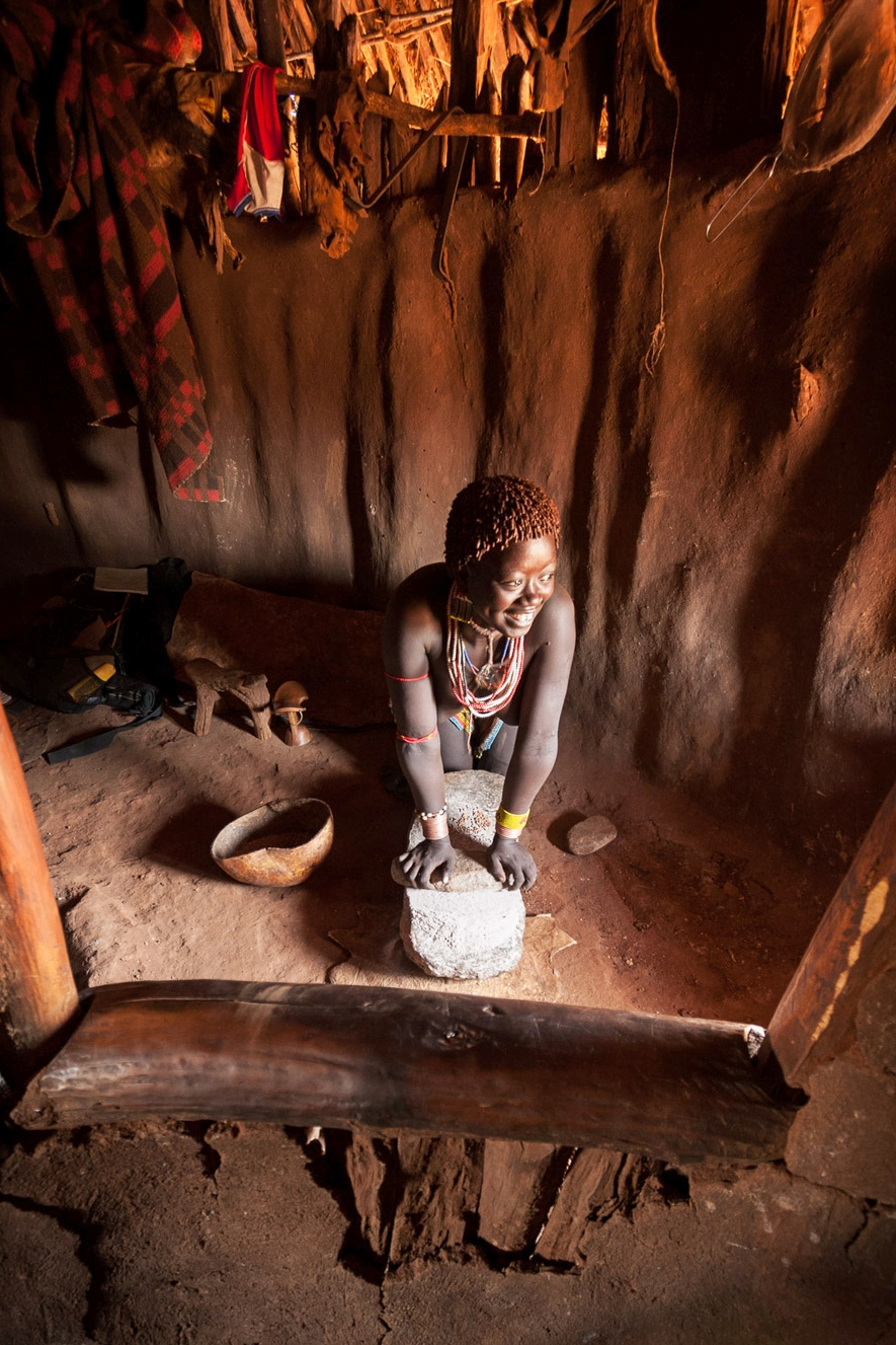 Grinding millet; Omo Valley, Ethiopia
