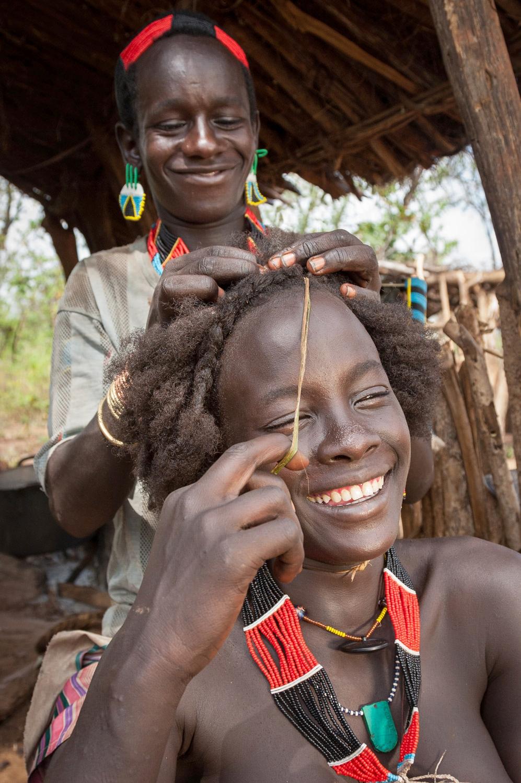 Bito fixes Bona's hair; Omo Valley, Ethiopia