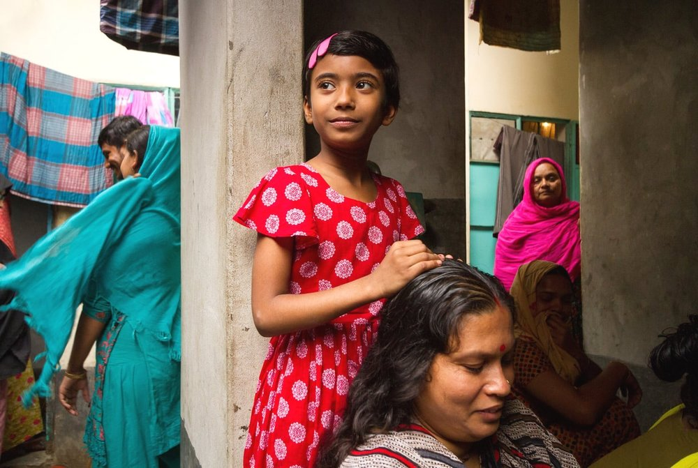 """Shushmita Rani, 7, stands behind her mother in the kitchen space they share with nine other families. Poor families place high hopes on their children to succeed in school and get a job. Shushmita's parents are no exception. """"It is important to send children to school and get them educated,"""" says her mother Anjoli Rani. """"Their father is a poor man. If they are educated they can get a job and we will be able to improve our standard of living, we will be able to grow. That is why children are sent to school."""""""