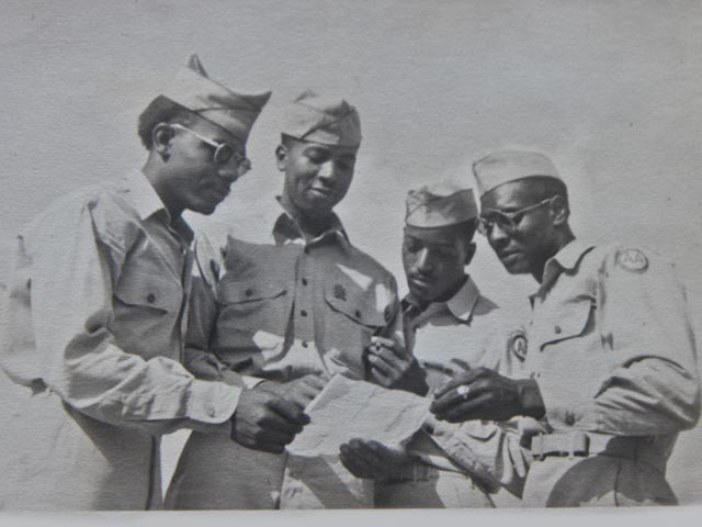 Wilson Monk (third from left) and other men from the 320th appear to be in deep thought as they peruse a document. Photo: Courtesy of Wilson Monk