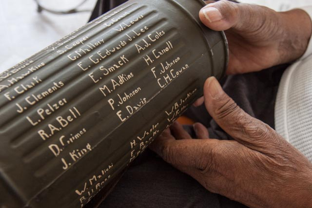 Wilson Monk points to the names of his friends painted on the canister of a German gas mask he found in Normandy in 1944. Photo: Linda Hervieux