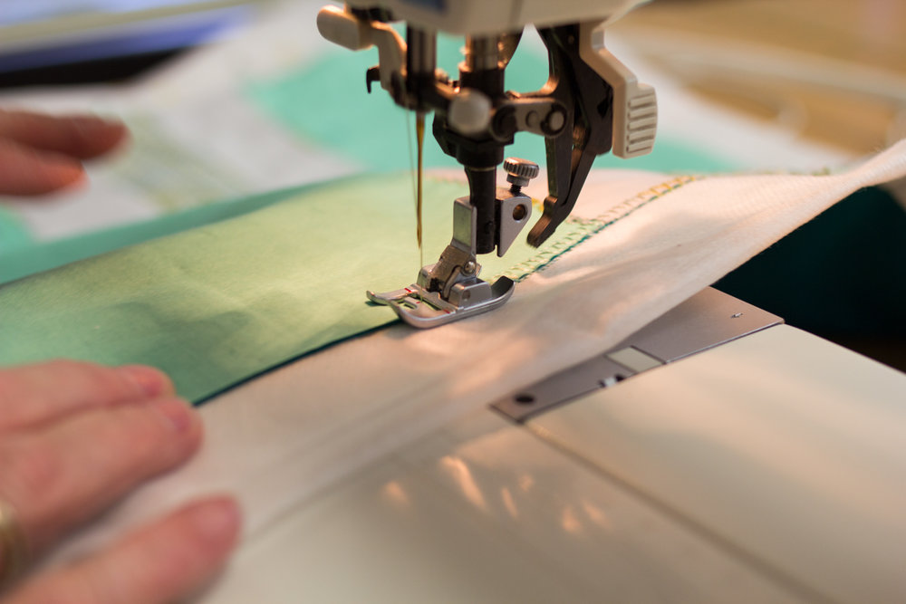 Stitching down the edge of the fabric.
