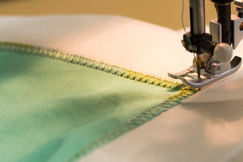 Stitching around the fabric with a satin stitch.