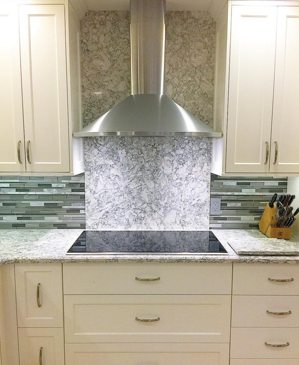 Cambria berwyn quartz countertops and backsplash with induction range cooktop and stainless steel range door. frameless white shaker cabinets