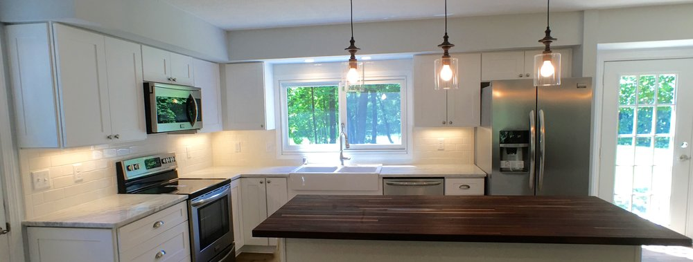 White kitchen with marble countertops, walnut butcher block, pendant lighting, stainless steel appliances, white farmhouse sink, subway tile backsplash, and under cabinet lighting