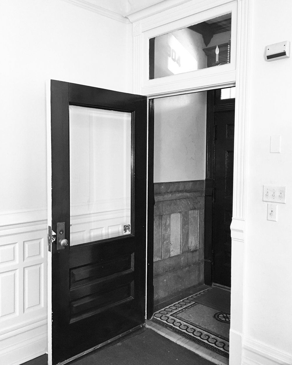 Glass & wood door & marble wainscoting in entry hall