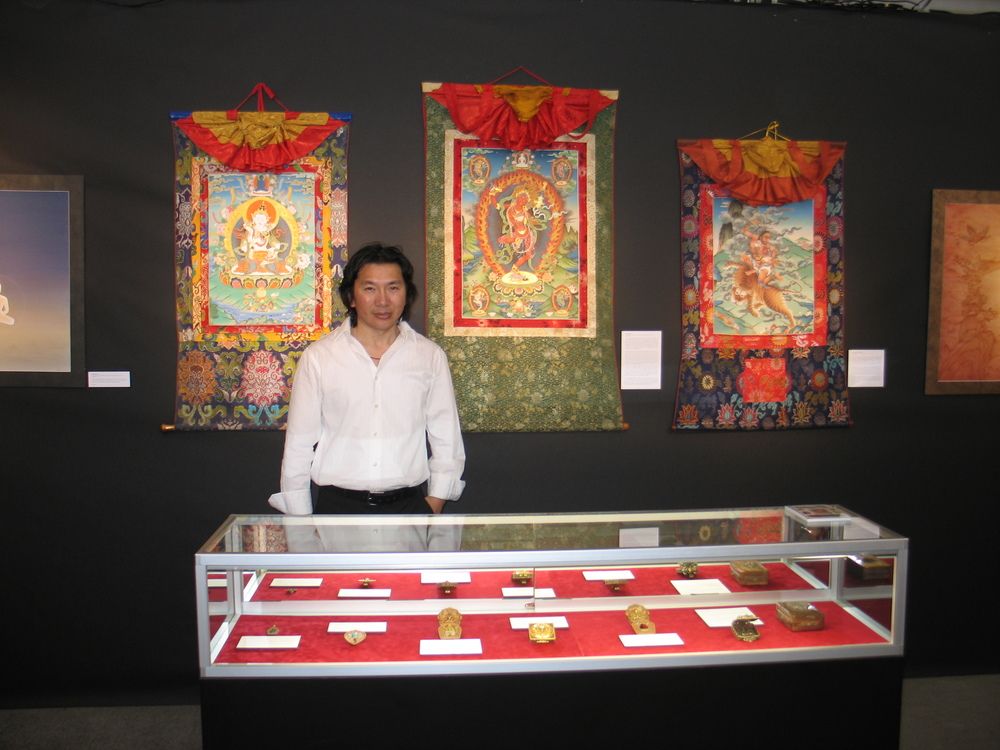 Pema Namdol displaying some of his gaus and dharma pendants at the San Francisco Arts of Pacific Asia Show