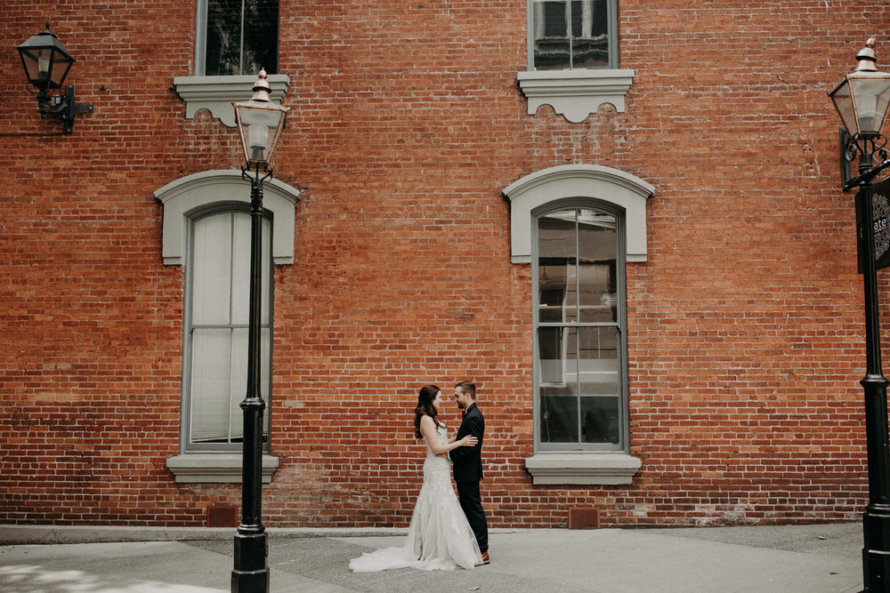 The bride and groom embrace each other during their first look in downtown Victoria.