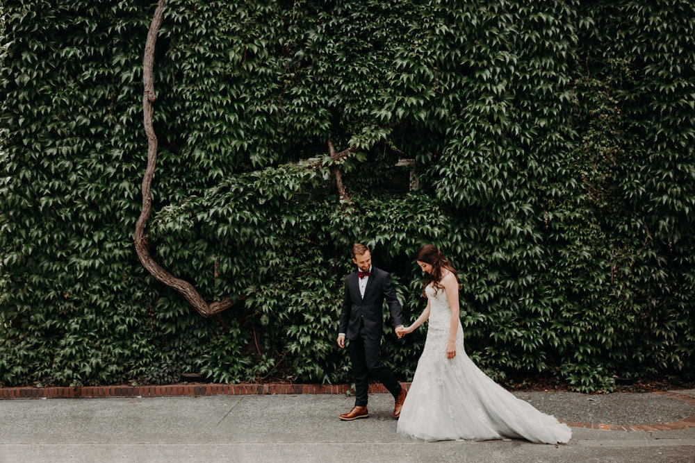 The bride and groom walk down a street in front of a wall of vines in downtown Victoria. Photographed by Candice Marie Photography.