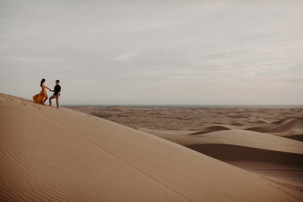 A couple standing at the top of a sand dune at the Glamis Imperial Sand Dunes near Palm Springs.