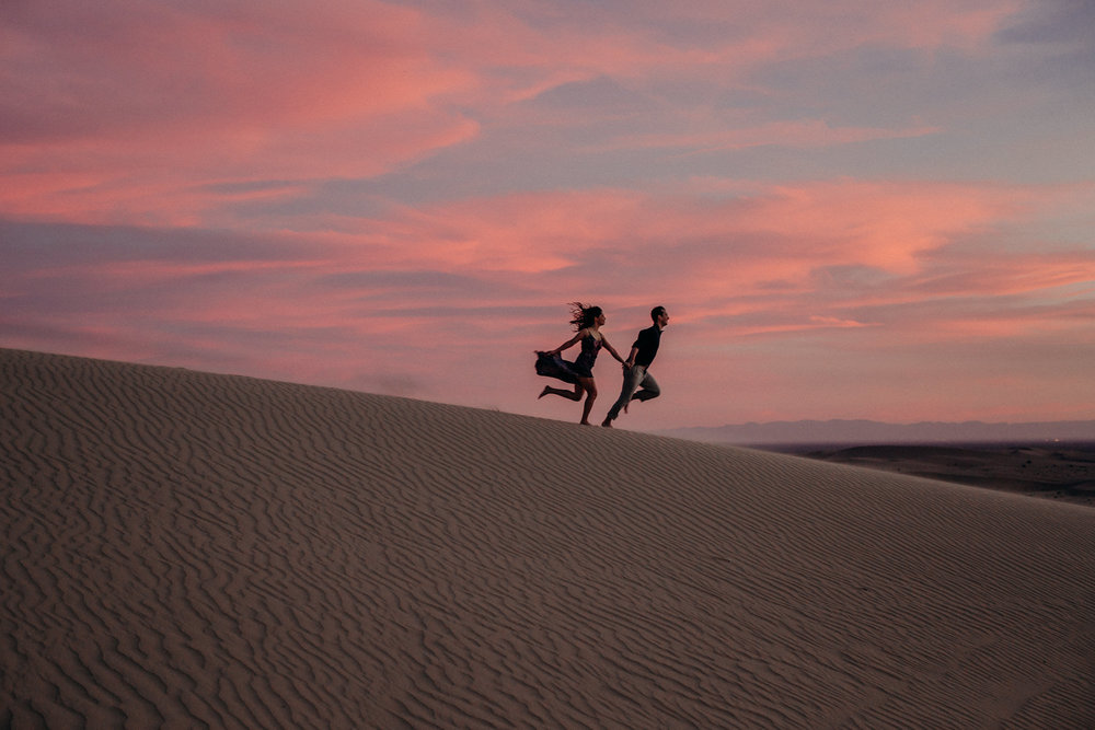 A silhouetted couple running down the sand dunes with a cotton candy sky behind them at the Glamis Imperial Sand Dunes. Photographed by Candice Marie Photography.