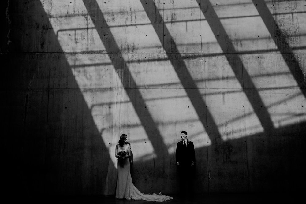 A photograph of a bride and groom standing in a mix of light and shadows in the parking garage on the campus of SAIT.