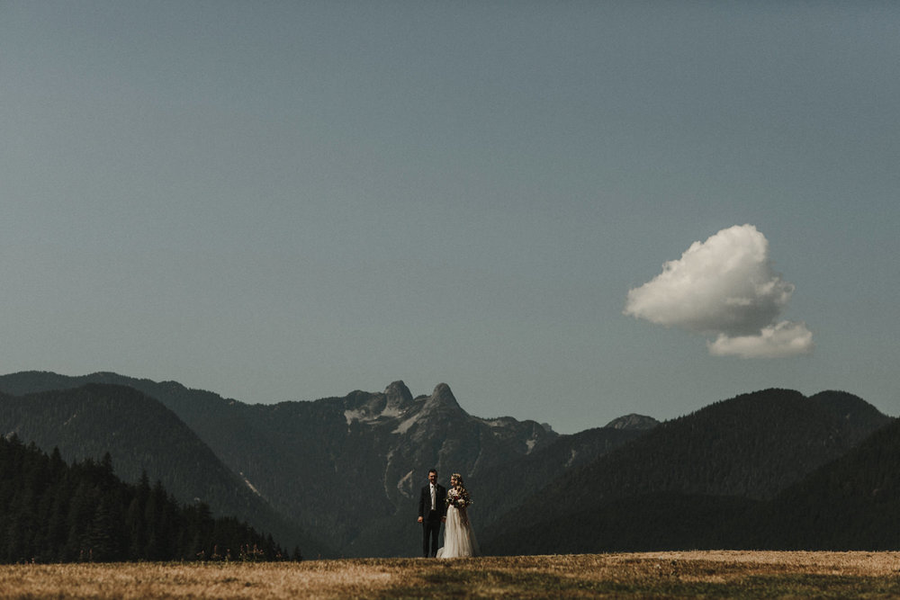 A wedding photo of a bride and groom in front of a mountain view at the Cleveland Dam.