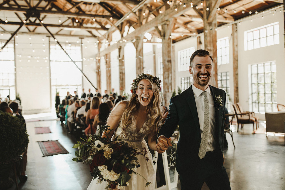 A happy couple exiting the ceremony with be smiles after being married at the Pipe Shop.