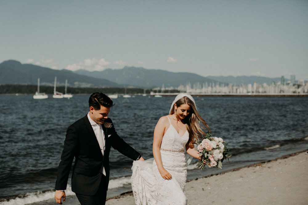 The bride and groom walk on the sand by the water at Jericho Beach in Vancouver, BC.