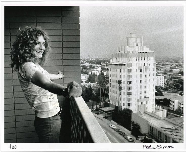 "Robert Plant in 1975, looking down from the Continental Hyatt balcony to a large billboard on Sunset Boulevard advertising the Led Zeppelin album ""Physical Graffiti."""