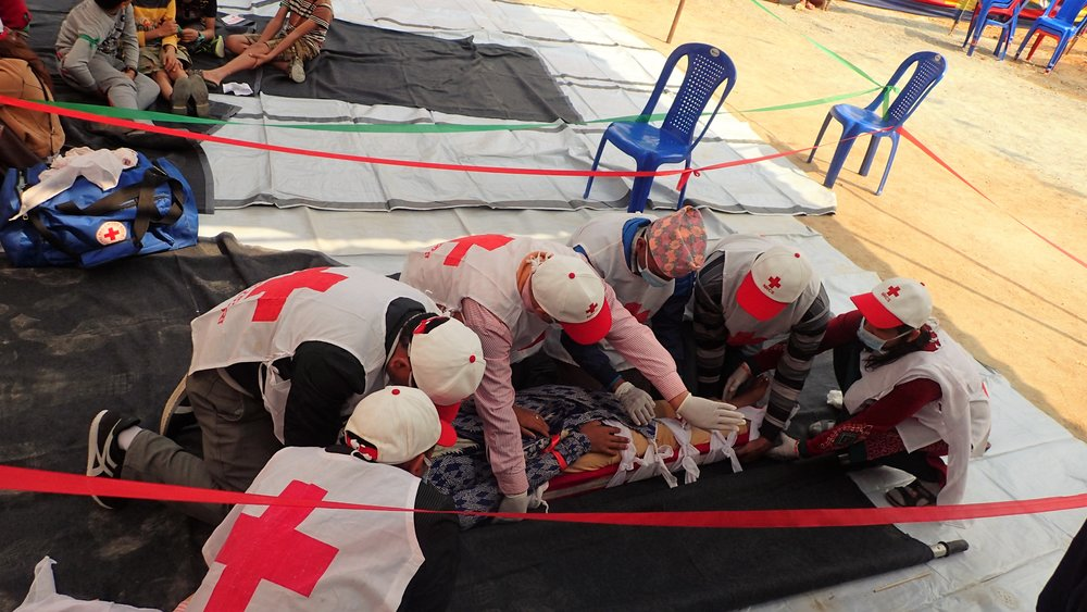 Red Cross giving first aid to injured people