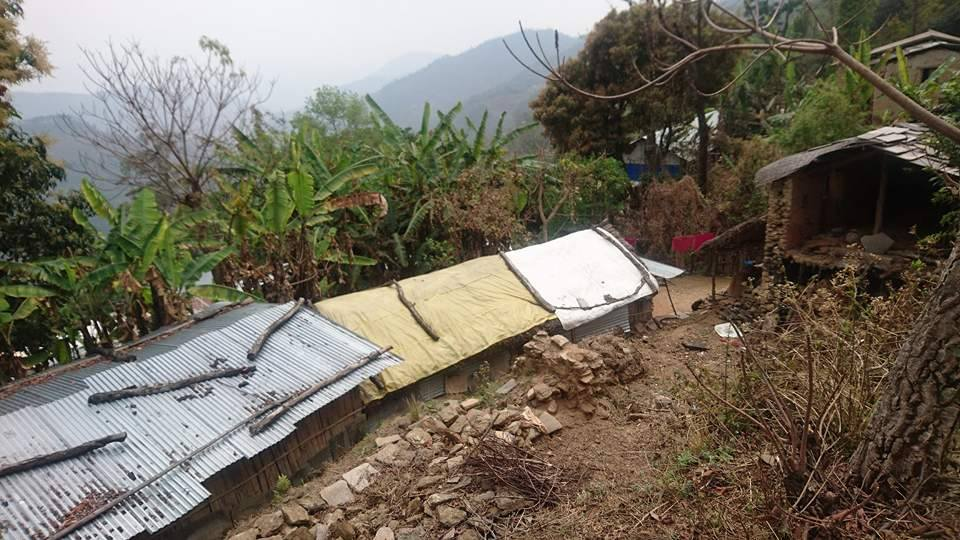 Temporary shelter next to house damaged by earthquake