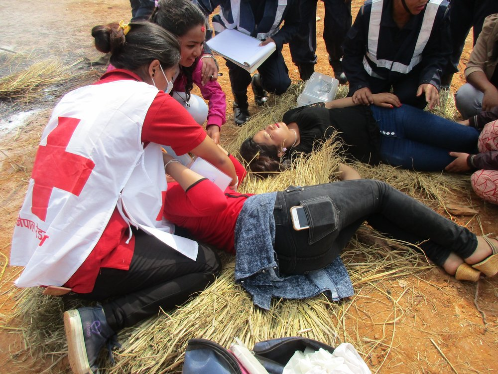 Red Cross volunteers helping wounded after eartquake.