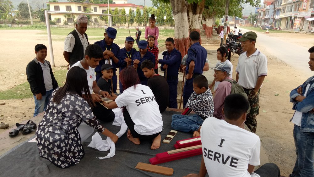 Youth volunteers teaching first aid to locals