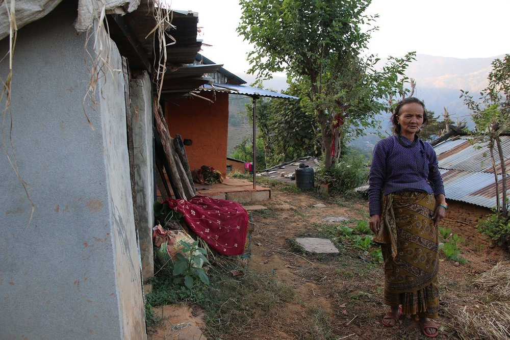 Local woman in front of her house, built by support of Norwegian Red Cross and local volunteers.  Photo: Roar Dalmo Moltubak/Røde Kors