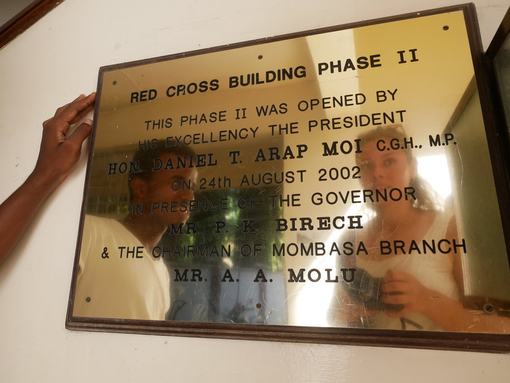 Entering the office, you are met with this plaque from the opening in 2002, when former President Moi was here to mark the event. In the reflection is Fayaz to the left, a Mombasa Branch volunteer and Elfi to the right. Photo: Elfi Thrane Bemelmans.