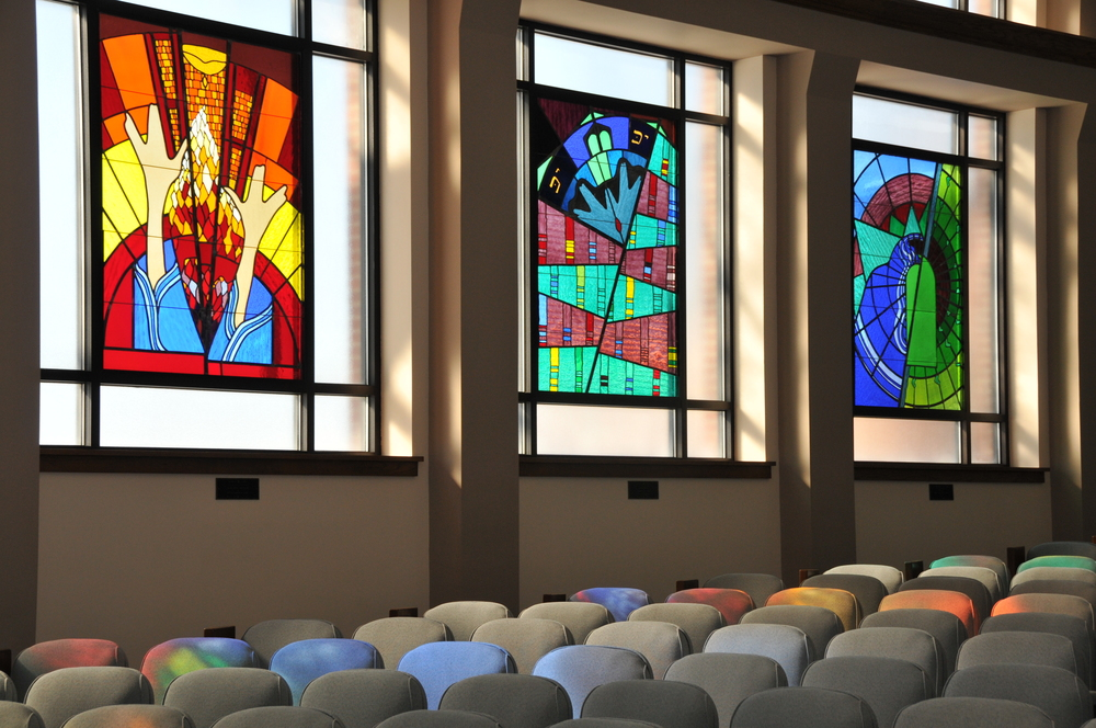 The sanctuary at Sinai Synagogue illuminated by the glow of sunlight through the stained glass windows.