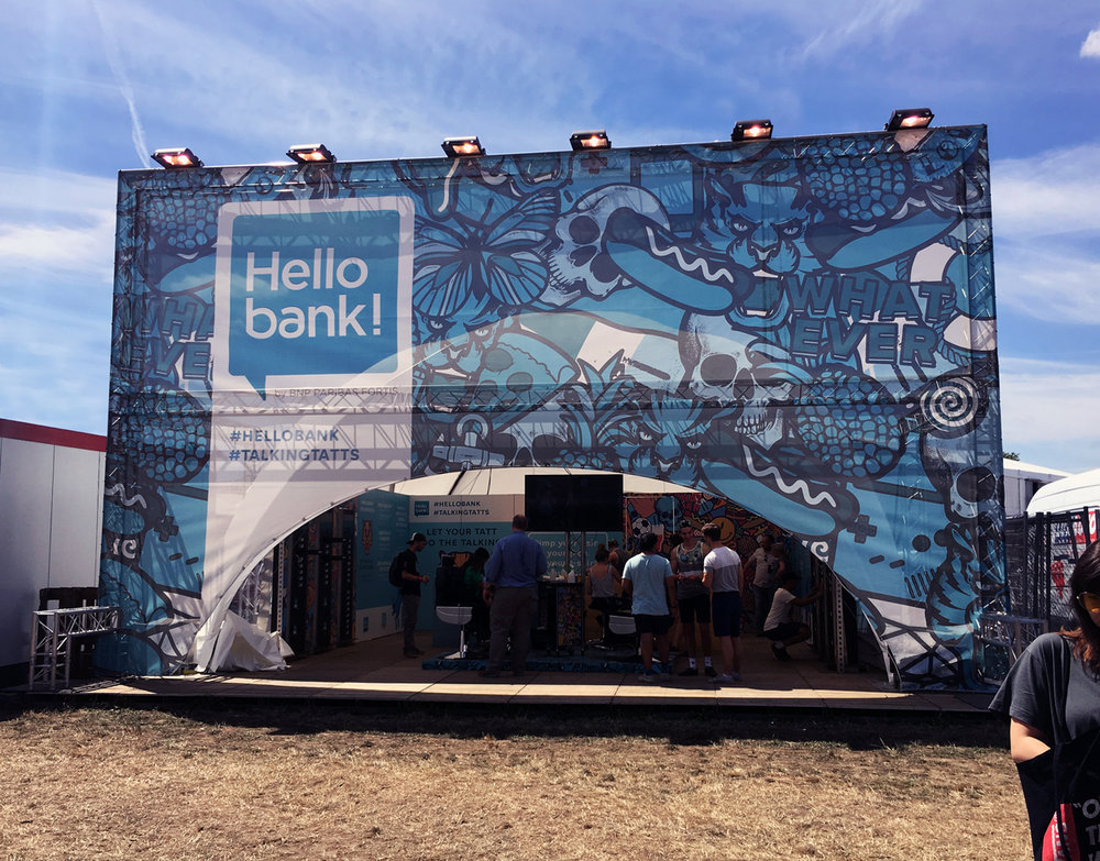 Exterior - Illustrations used as a pattern with a blue overlay to match the brand colours of Hello Bank. Festival visitors could enter to get a free Musketon sticky tattoo at Dour and Pukkelpop festival.