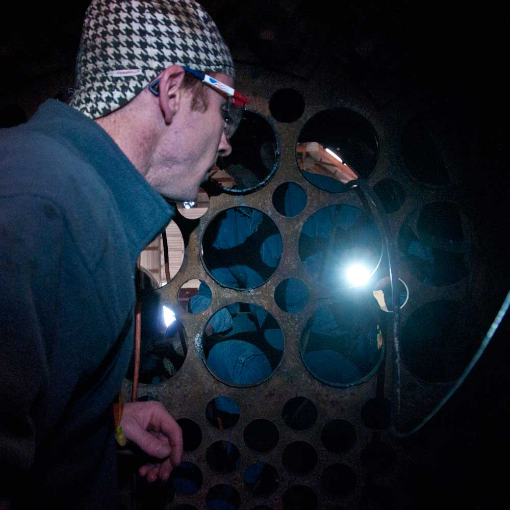 "Shane Meador inspects the large 5-1/2"" superheater openings in the front flue sheet of 152."