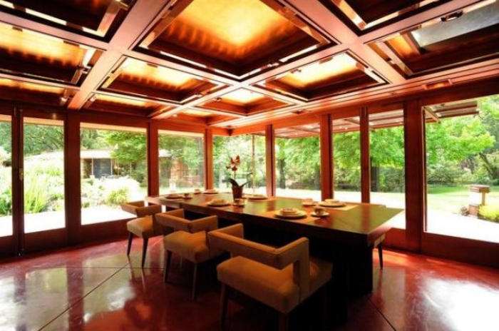 """If you're seeking a smashing venue for a personal celebration or a company soiree, this is the place,"" the website continues.  The dining room of the Maynard Buehler house, built in the late 1940's by Frank Lloyd Wright in Orinda, Calif. features low-back seats designed by the architect to not interfere with the view of the outside gardens. Photograph taken Thursday July 14, 2011. (Karl Mondon/Staff)"