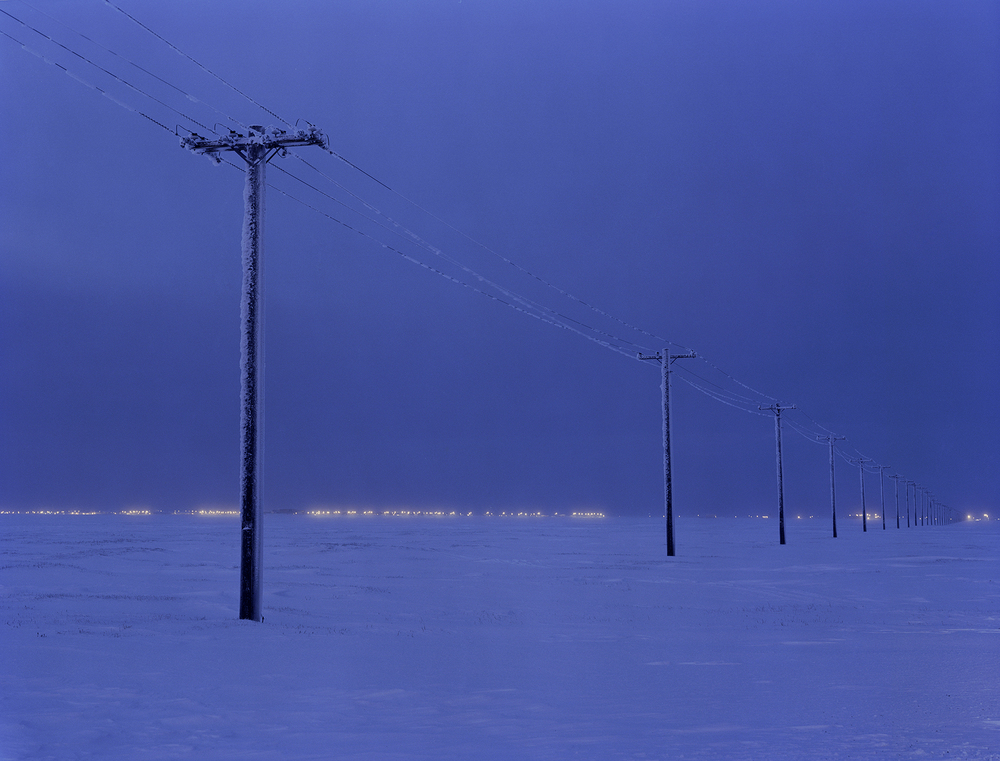 "CHRISTINA SEELY Metra Simulti:  Luminaria 71º N: Midday Winter Apex/ Industrial  Archival Inkjet Print 24 x 30 inches Edition of 4   Midday at the apex of 90 days of arctic winter darkness is shown, while electricity is used by residents to extend and control the ""day time"" cycle."