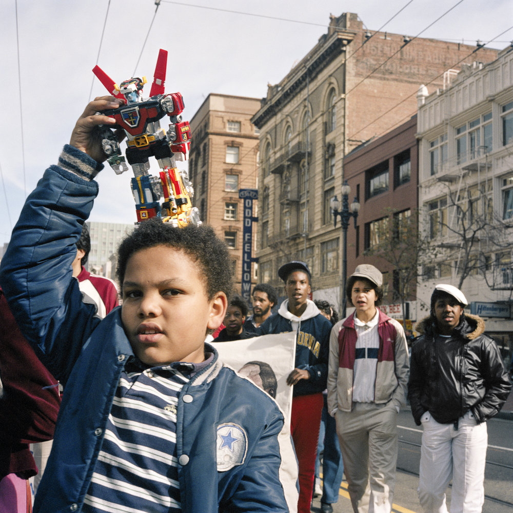 JANET DELANEY  Boy with Voltron, First Martin Luther King Day Parade,  1986 from  Public Matters  Archival Pigment Print, 2018  Available in 3 sizes 9 x 9 inches, edition of 7 + 2AP 15 x 15 inches, edition of 3 + 2AP 22 x 22 inches, edition of 2 + 1AP