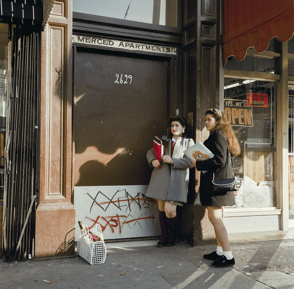 JANET DELANEY  Two School Girls, Mission Street,  1985 from  Public Matters  Archival Pigment Print, 2018 9 x 9 in. Edition of 7 + 2AP