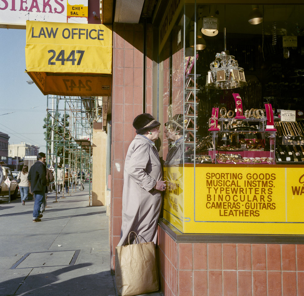 JANET DELANEY  Woman Looking in Pawn-shop, Mission Street,  1984 from  Public Matters  Archival Pigment Print, 2018 9 x 9 in.; frame: 15 x 15 in. Edition of 7 + 2AP