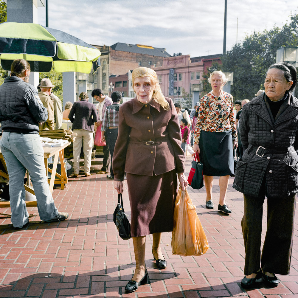 JANET DELANEY  Woman in Brown Suit at the Heart of the City Farmers Market,  1983 from  Public Matters  Archival Pigment Print, 2018 9 x 9 in.  Edition of 7 + 2AP