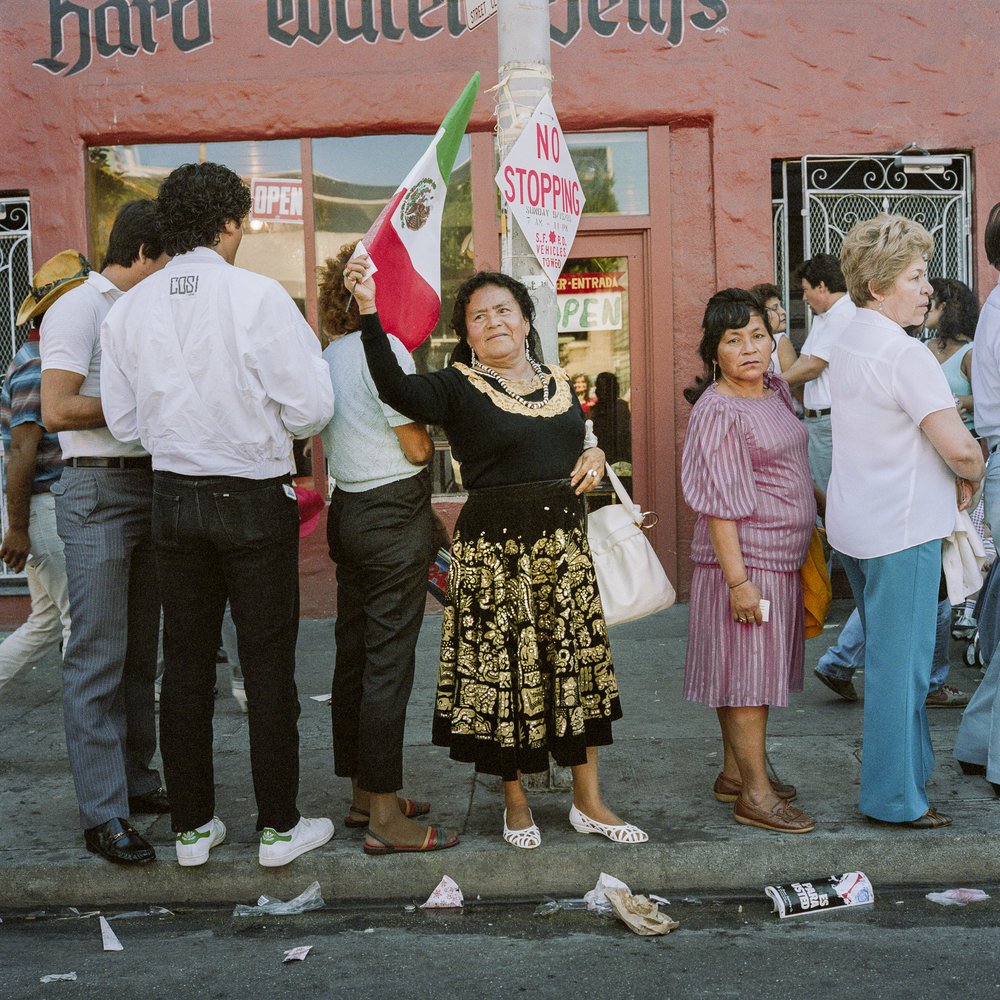 JANET DELANEY  Woman with Mexican Flag, 24th Street,  1985 from  Public Matters  Archival Pigment Print, 2018 9 x 9 in.  Edition of 7 + 2AP