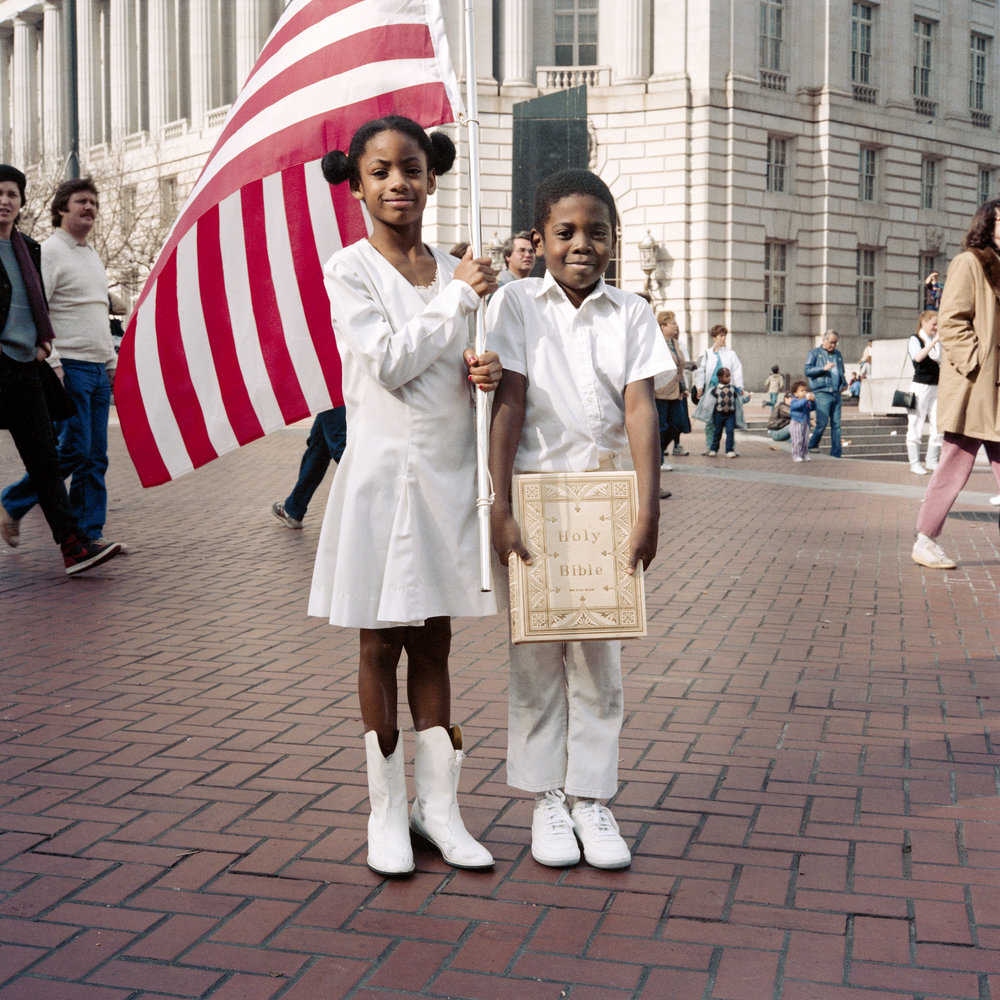 JANET DELANEY  American Flag and Holy Bible, 1986  from  Public Matters  Archival Pigment Print, 2018  Available in 3 sizes 9 x 9 inches, edition of 7 + 2AP 15 x 15 inches, edition of 3 + 2AP 22 x 22 inches, edition of 2 + 1AP