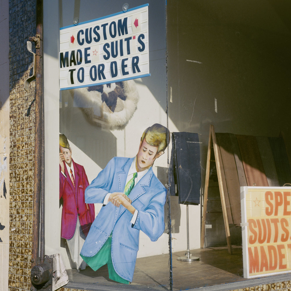 JANET DELANEY  Custom Suits, Mission Street, 1984  from  Public Matters  Archival Pigment Print, 2018  Available in 3 sizes 9 x 9 inches, edition of 7 + 2AP 15 x 15 inches, edition of 3 + 2AP 22 x 22 inches, edition of 2 + 1AP